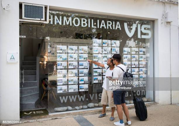 Two tourists look at apartments in the window shop of a real estate on the island of Ibiza on August 11 2017 Known as much as a wild party island as...