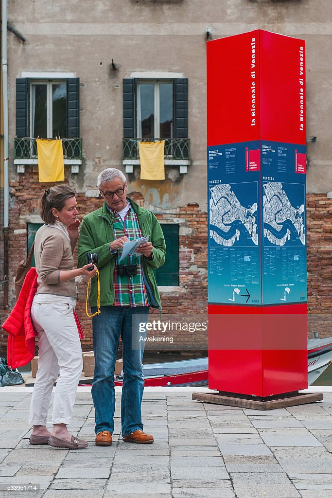 Two tourists look at the map near a street sign of the 15th Architecture Venice Biennale, on May 24, 2016 in Venice, Italy. The 56th International Architecture Exhibition of La Biennale di Venezia will be open to the public from May 28, 2016 in Venice, Italy.