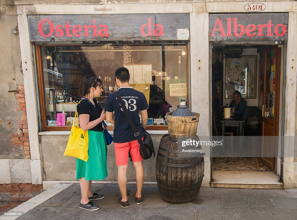Two tourists look at the window in front of a traditiona bacaro at 'Osteria da Alberto' bacaro on June 30, 2016 in Venice, Italy. The bacari which opens for lunch and dinner are the local down to earth version of a wine bars. Venetians stop to snack and enjoy 'ciccheti, a kind of Tapas traditionally washed down with a glass of wine.