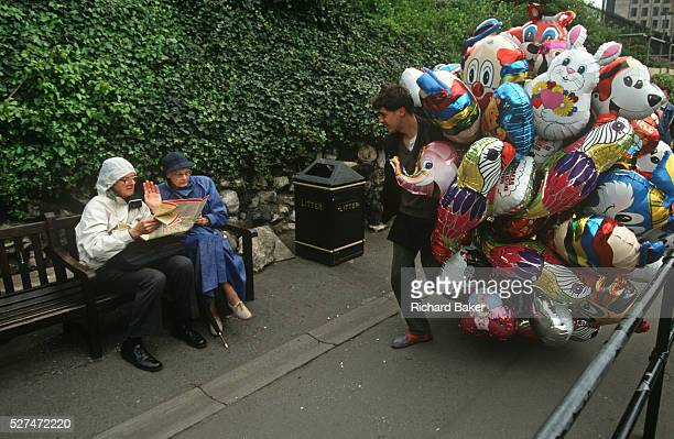 Two tourists reading a street map refuse the chance to buy a helium balloon from a street vendor near the Tower of London A man selling a huge bundle...