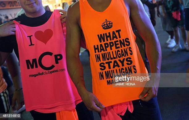 Two tourists show their club promoting tanktops in Punta Ballena street in Magaluf holiday resort in Calvia on the Spanish Mallorca Island on July 19...