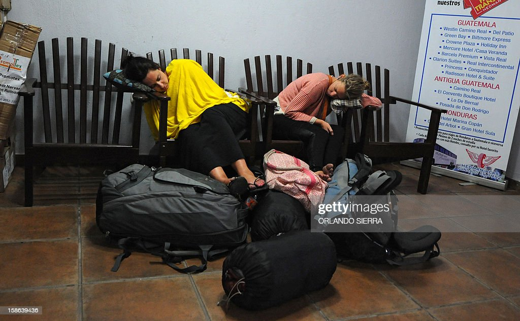 Two tourists sleep at the bus terminal in Copan Ruinas, 400 km northeast of Tegucigalpa, on December 22, 2012, after attending a ceremony to celebrate the end of one Mayan cycle and the start of a new one. A global day of lighthearted doom-themed celebration and superstitious scare-mongering culminated on December 21 at the temples of the Mayan people, whose calendar sparked fears of apocalypse. December 21 marked the end of an era that lasted 5,200 years, according to the Mayan 'Long Count' calendar. AFP PHOTO / Orlando SIERRA