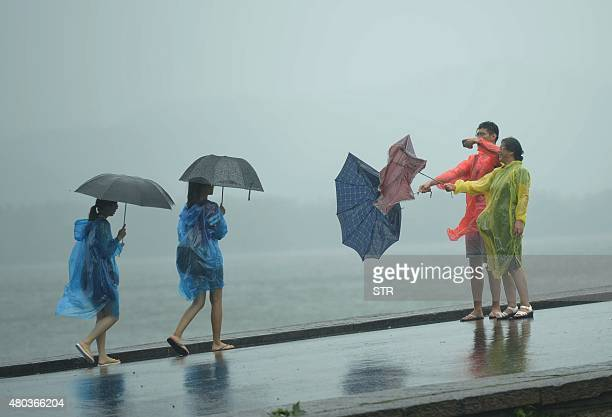 Two tourists take a photograph of their broken umbrella amid a heavy storm brought by typhoon Chanhom in Hangzhou east China's Zhejiang province on...