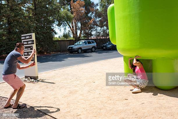 Two tourists take photographs with a large statue representing the Android cellphone operating system at the Googleplex headquarters of the search...