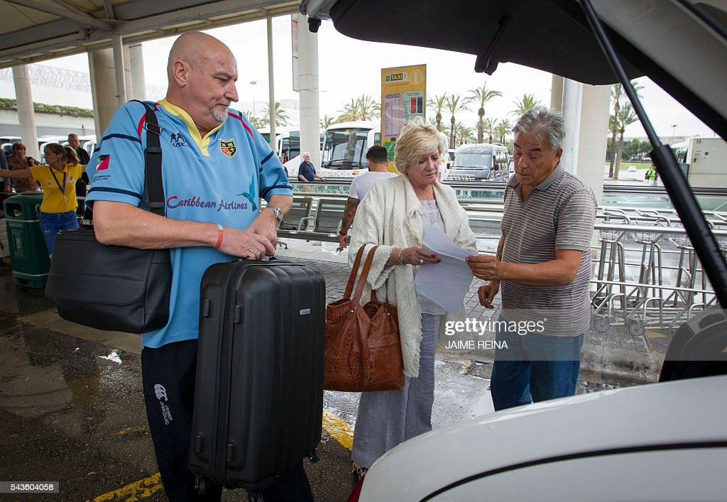 Two tourists talk to a taxi driver at the Palma de Mallorca airport on June 29, 2016. As of July 1, 2016 the Balearic Island government brings launches an Ecotax, 'Ecotasa', targeting tourism businesses that will onpass the daily 0.25 Euro to two euro levy onto their clients. REINA
