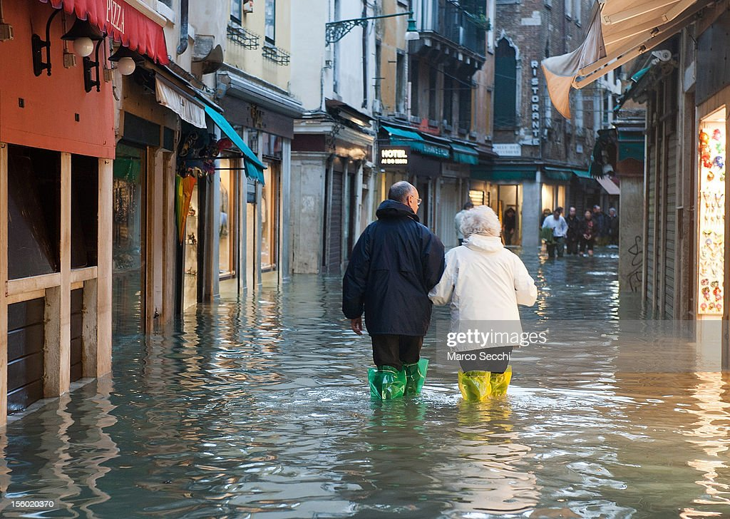 Two tourists walk in the shopping area of Venice during the exceptional High Water on November 11, 2012 in Venice, Italy. More than 70% of Venice has been been left flooded, after the historic town was hit by exceptionally and unexpected high tide. The sea level rose very quickly to 150 due as well to strong southerly wind and heavy rain.