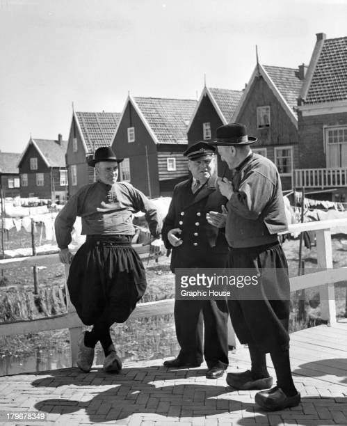 Two townsmen exchange news with a boat captain who brings mail to the Island of Marken Holland