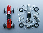 Two toy cars, one assembled, one in pieces, close-up, overhead view
