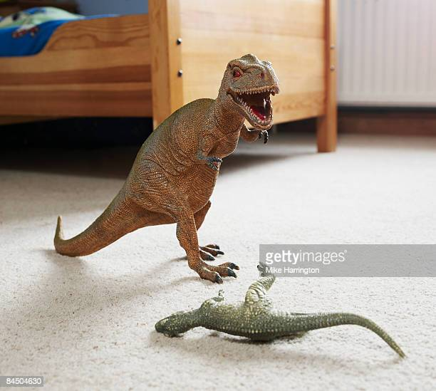 Two toy dinosaurs fighting in childs room