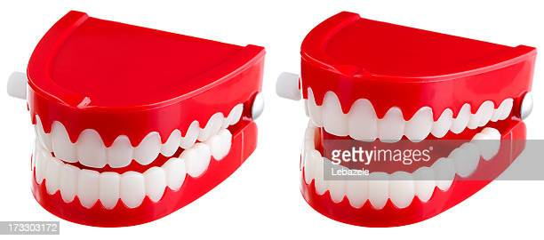 Two toy wind-up chatter teeth on a white background