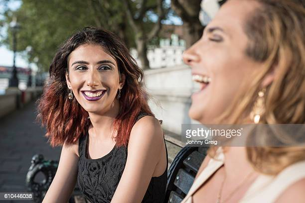 Two transgender female friends laughing outdoors