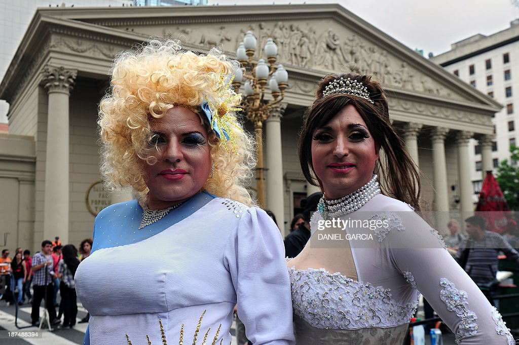Two transvestites pose for a picture at Plaza de Mayo in front of the Metropolitan Cathedral during the XXII Gay Pride Parade in Buenos Aires on November 9, 2013.