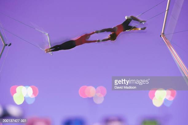 Two trapeze artists performing release move (Digital Composite)