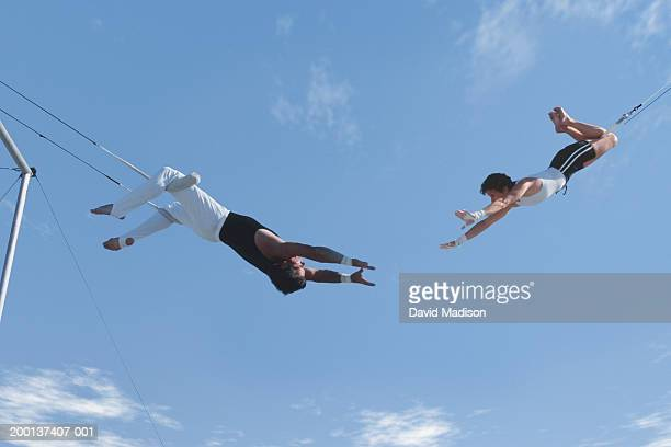 Two trapeze artists swinging towards one another, outdoors