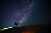 two travellers with flash light stand on sand dunes hill and look at the milky way on starry night sky , with copy space on sky