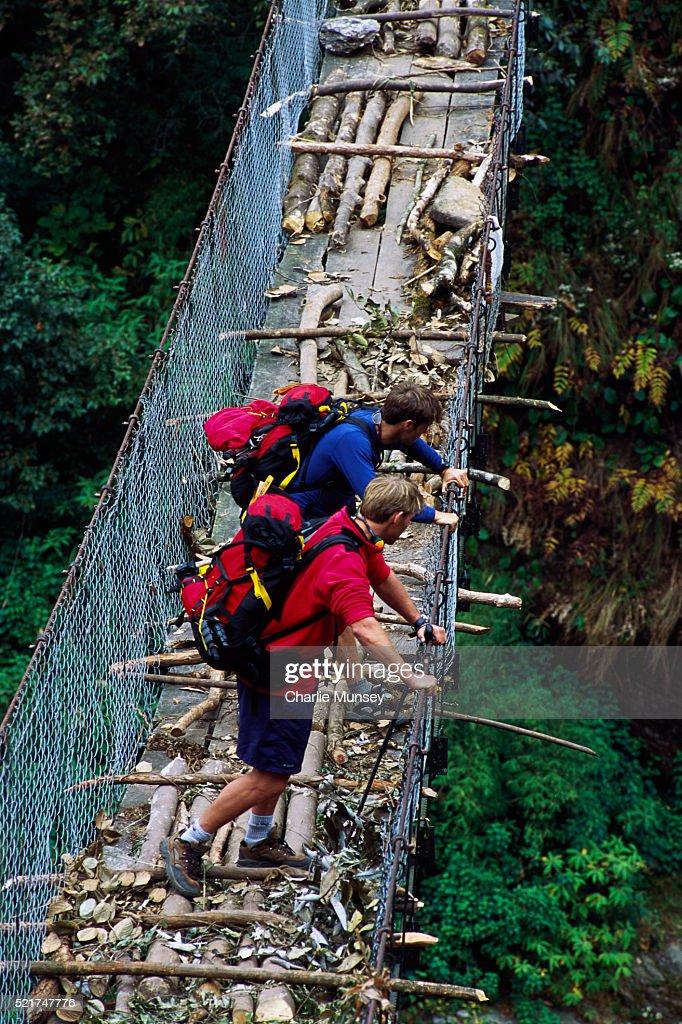 Two trekkers take a break on swing bridge in the Himalayas of Nepal. MR: C1- Reggie Crist M2- Gerry Moffatt