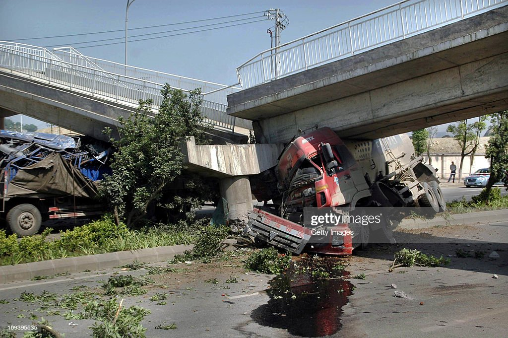 Two trucks are pinned under a collapsed overbridge on May 23, 2013 in Guiyang, China. An overbridge collapsed when a tank truck crashed and broken a concrete support on west second ring road on Thursday morning, hitting another passing truck and injuring two drivers.