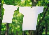 Two T-shirts hanging side by side on a washing line