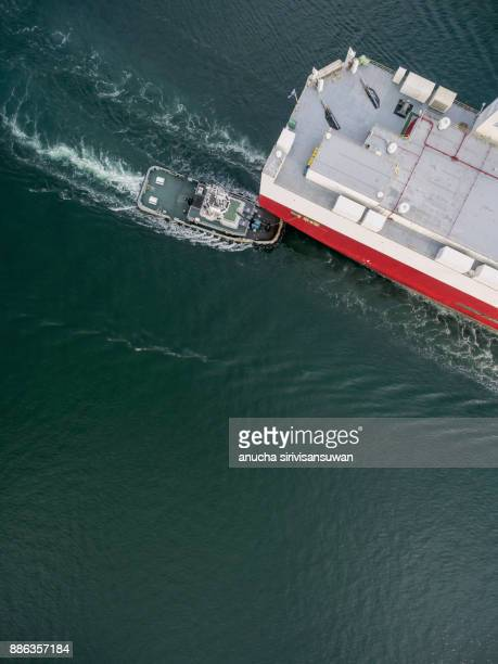 two tug boat towing car carrier ship go to dock .