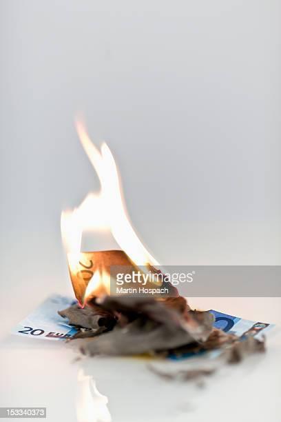 Two twenty euro banknotes on fire