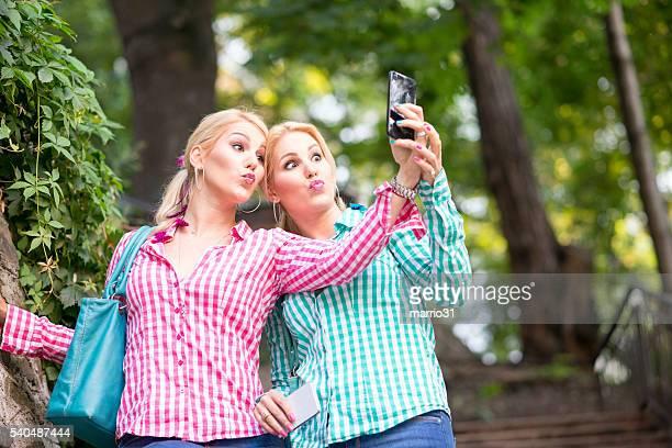 Zwei Schwestern, die mit Smartphone selfie
