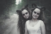 Two twins demons with horns in forest outdoor