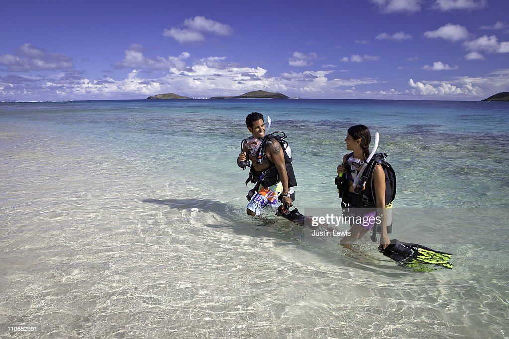 two two divers walking out of water in tropics : Stock Photo
