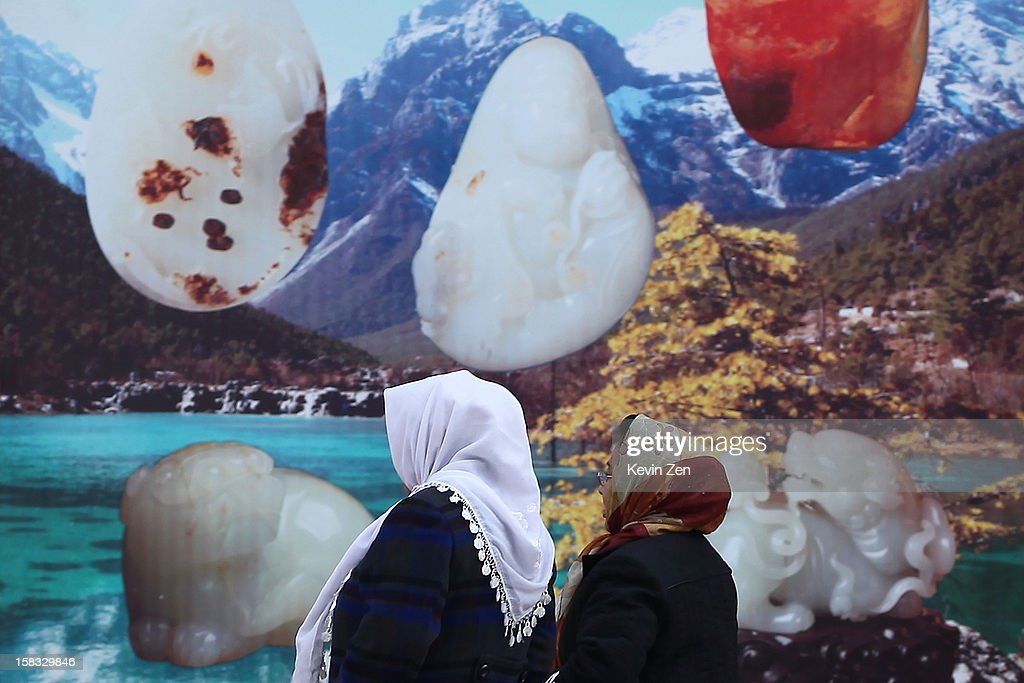 Two Uighur women walks by a jade photo wall in Kashgar, on December 10, 2012 in Kashi, China. Kashgar is home to the ethnic Uyghur Muslim community.