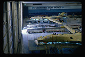 Two unfinished B1B Lancer bombers in an assembly plant at Air Force Plant 42 California A sign on the wall reads 'Prepared for Peace'