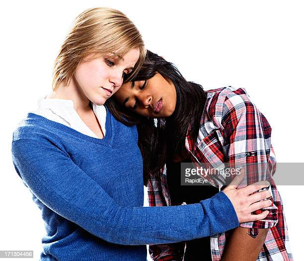 Two unhappy-looking young women console each other