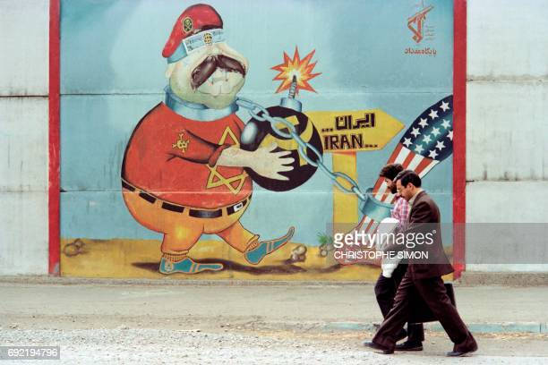Two unidentified Iranians walk past a satirical wall painting showing a blindfolded Israel with bomb near the Tehran airport on October 25 1989 / AFP...
