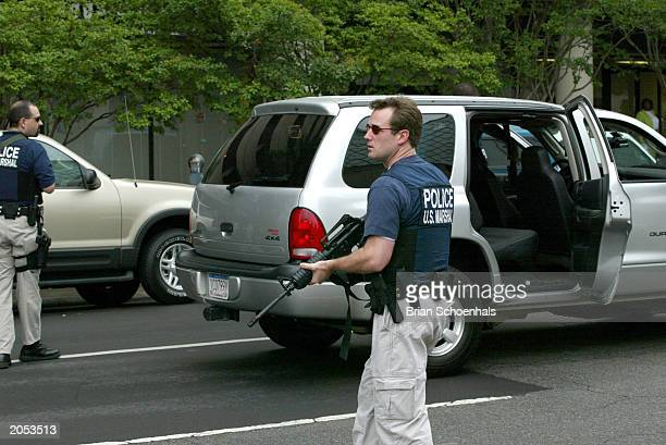 Two unidentified US marshals stands guard as a car carrying Eric Rudolph leaves the federal courthouse June 3 2003 in Birmingham Alabama Rudolph...