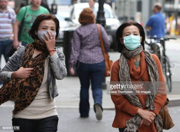Two unidentified women walk through Manchester city centre wearing antipollution masks