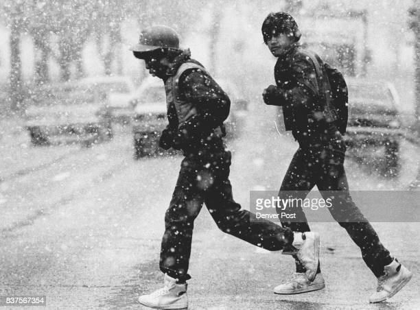 Two unidentified young men run across Speed Blvd downtown while the spring snow flakes come down Credit The Denver Post