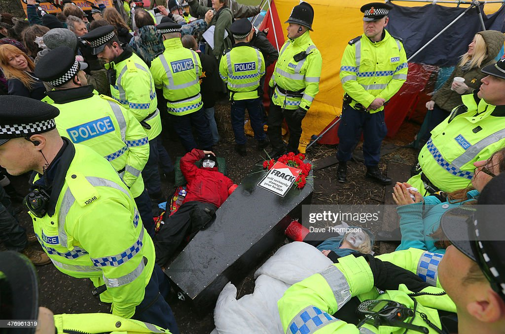 Two unnamed antifracking protesters lie in the road surrounded by police after engaging in a 'lockon' near the Barton Moss exploration facility on...