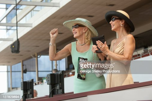 Two upscale ladies cheering at horse race