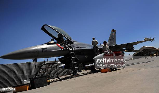 Two US Airforce grounstaff inspect a F16 fighter jet at the Bagram Airbase in the Parwan province some 50 kms north of Kabul on August 10 2009 The...