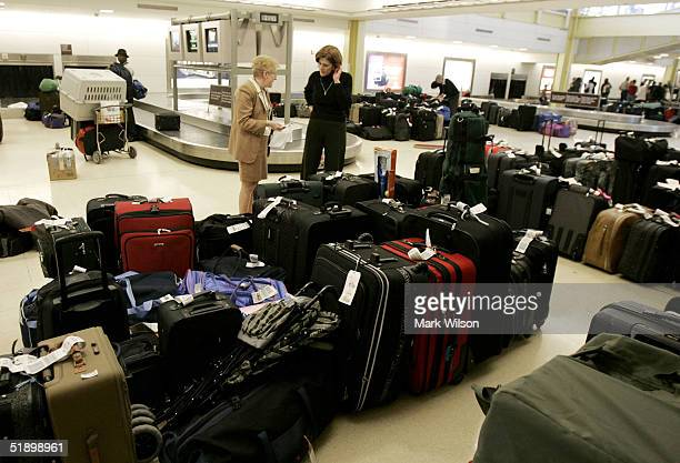 Two US Airways employees speak to each other as they sort lost luggage in front of the US Airways baggage service office at Ronald Reagan Airport...