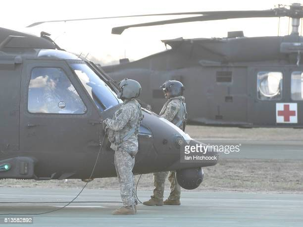 Two US Army Blackhawk helicopter crewman perform pre flight checks before take off at the Williamson airfied in the Shoalwater Bay Training Area as...