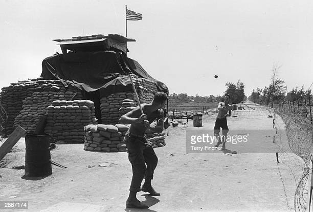 Two US Marines play a makeshift game of baseball with a trimmed stick as a bat and a ration can as the ball outside the sandbagged bunker that guards...