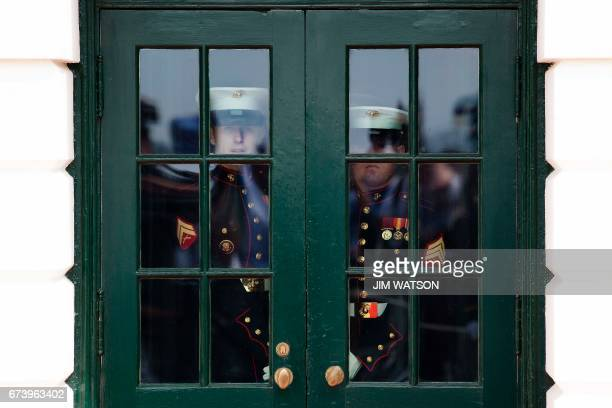 Two US Marines wait to open the doors of the South Portico as they prepare for US President Donald Trump to welcome Argentinian President Mauricio...