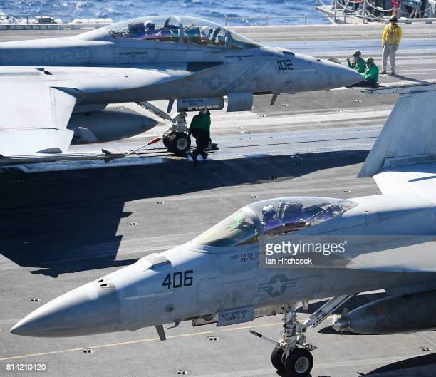 Two US Navy Super Hornets are seen moving into position prior to launching from the deck of the USS Ronald Reagan on July 14 2017 in Townsville...