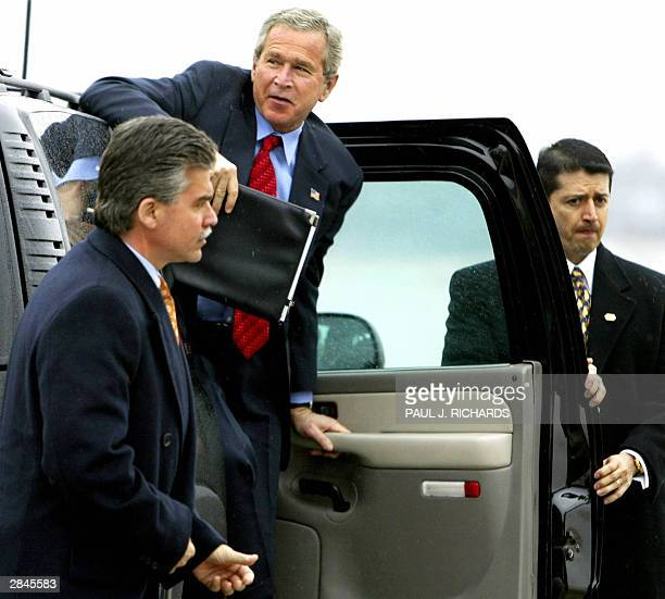 Two US Secret Service Agents stand at the ready as US President George W Bush climbs out of his SUV instead of his normal limousine 05 January 2004...
