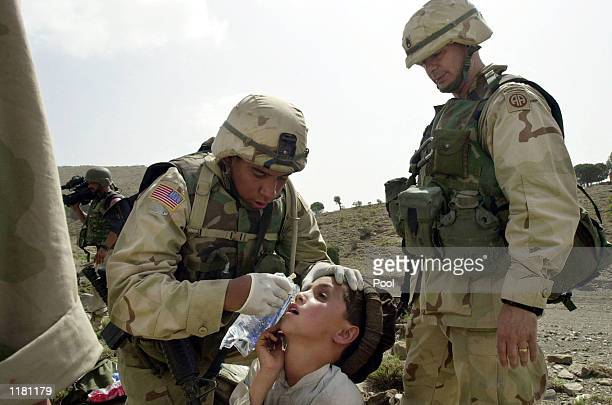 Two US soldiers of the 401st Airborne Battalion apply treatment to a young Afghan boy suffering from conjunctivitis or 'Pink Eye' July 29 2002 in...