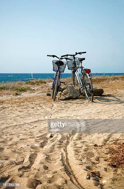 Two vacant bicycles' peddlers invisibly meddle on the beach