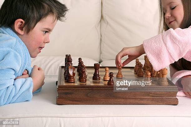 Two very smart kids playing chess after just waking up