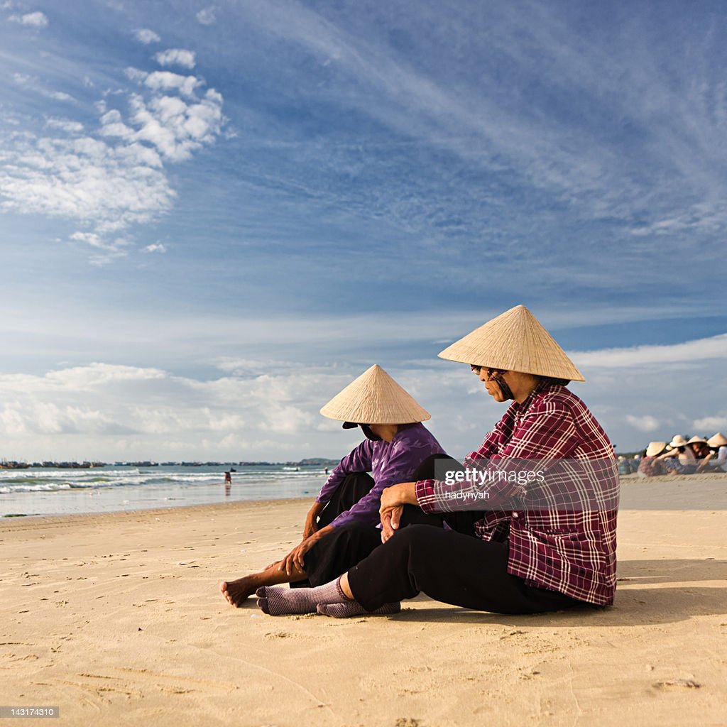 Two Vietnamese women sitting on the beach : Stock Photo