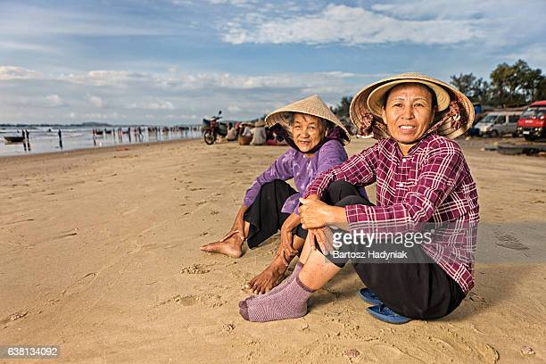 Two Vietnamese women sitting on the beach