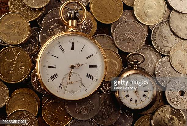 Two vintage clock faces and coins, full frame