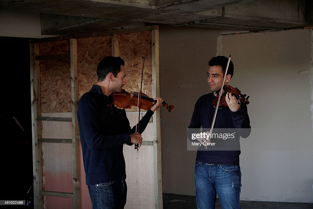Two violinists from the MultiStory Orchestra practice before a performance of Jean Sibelius' 5th Symphony at the Peckham Rye Car Park on June 21 2014...